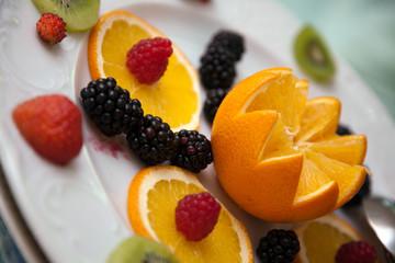 Arancia tagliata a fiore e frutti rossi in primo piano