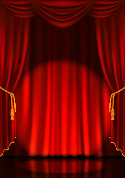 Theater stage with red curtains and spotlight.