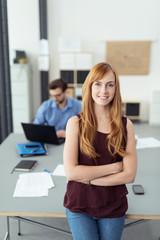 motivierte mitarbeiterin lehnt an ihrem schreibtisch im büro