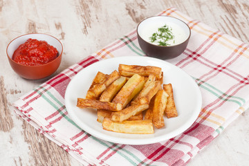 fried french fries with tomato sauce and herbs, close-up