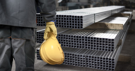worker with helmet in front of steel metal profiles
