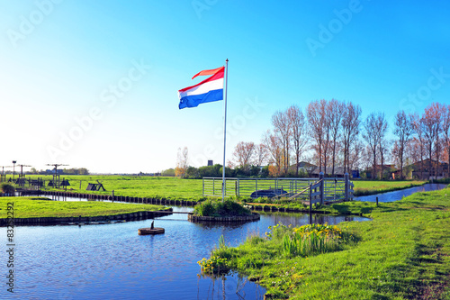 typical dutch landscape with the dutch flag in netherlands stock