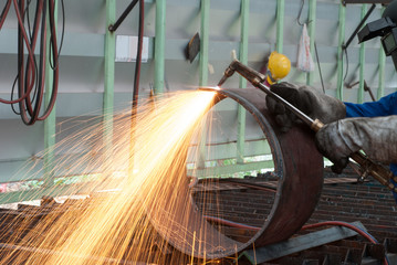 worker in factory cutting steel pipe using metal torch