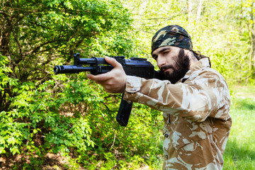 Bearded soldier with a rifle in the woods