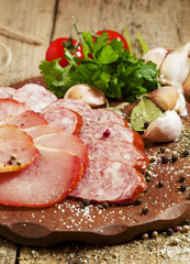 Slices of smoked ham and sausages on a cutting board in a rustic