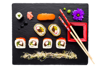 Sushi on black stone plate isolated top view