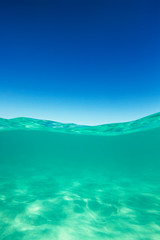 Clear waterline caribbean sea underwater and over with blue sky