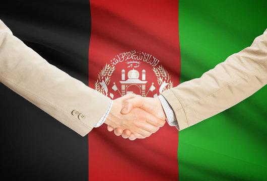 Businessmen handshake with flag on background - Afghanistan