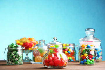 Colorful candies in jars on table on blue background