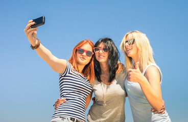 Happy girlfriends taking selfie on blue sky in summer vacation