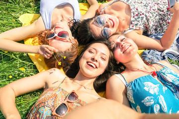 Multiracial girlfriends taking selfie at countryside picnic