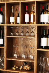 Shelving with wine bottles with glasses on wooden wall background