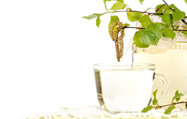 A transparent cup of birch sap with birch leaves