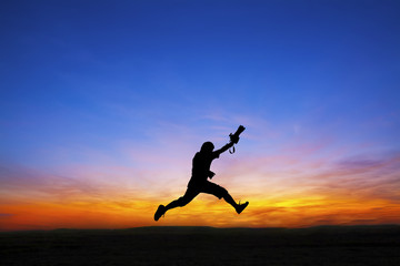 Silhouette of photographer jumping at sunset time