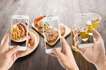 friends using smartphones to take photos of sausage and pork cho