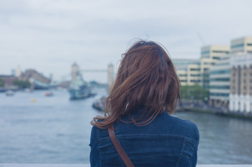 Young woman standing on a bridge and looking at city