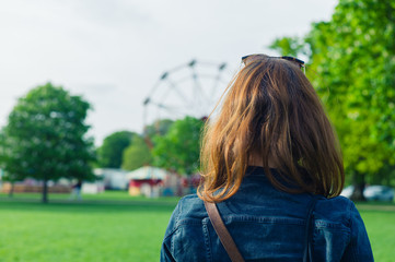 Woman in park looking at fun fair