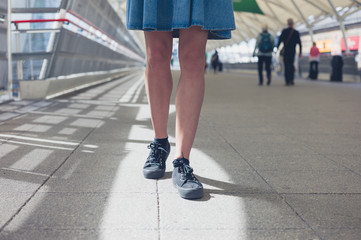 Legs of young woman walking in station