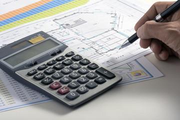 Businessman hand holding pen on blueprint
