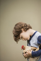 A small boy holding a chicken in his arms.