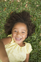 A girl lying on her back on grass, smiling and looking up.