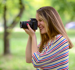 Portrait of beautiful laughing brunette girl taking photos at pa