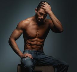 Muscular guy in blue jeans