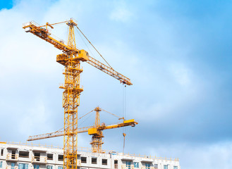Yellow cranes work in modern houses massive