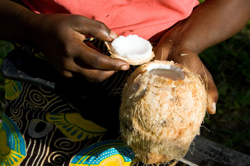 Woman shows opened coconut, which she opened with a machete.