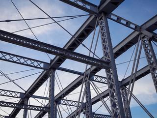 Detail of painted riveted bridge against blue sky.