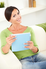Young woman toothy smiling while holding a tablet