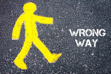 Yellow pedestrian figure walking towards WRONG WAY