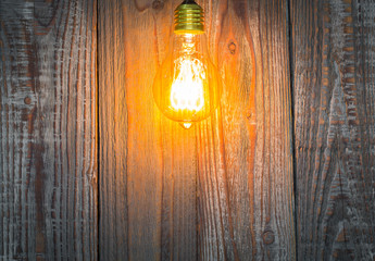 Glowing bulb on the wood background