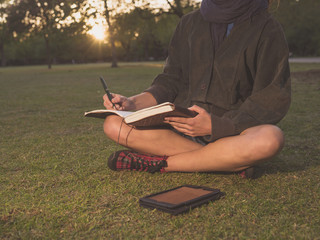 Woman on grass with tablet and notebook in park