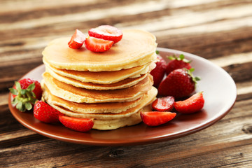 Delicious pancakes with strawberry on brown wooden background