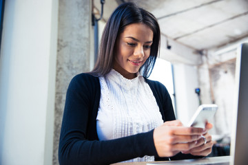 Smiling businesswoman using smartphone in cafe