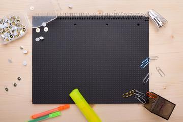 Büromaterial und schwarzes Papier