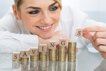 Businesswoman With Savings Blocks On Coins