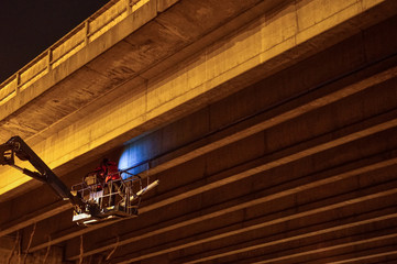 Arbeiter in der Nacht an der Autobahnbrücke