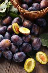Fresh plums on brown wooden background
