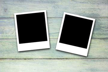 Blank photo frames on wood background