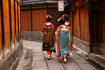 Three geishas walking on a street of Gion (Kyoto, Japan)