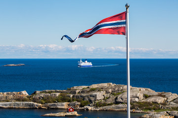 Norwegian flag with a small red cabin and an unmarked ferry