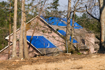 tornado damaged house with a blue tarpaulin on the roof