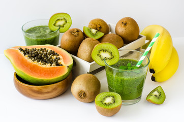 Green tropical smoothie with kiwi, papaya and bananas white back