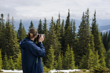 young caucasian man with camera outdoors in mountains
