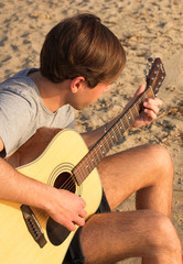 Practicing in playing guitar on a beach