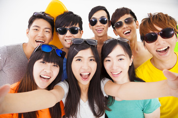 group of smiling friends with camera  taking selfie