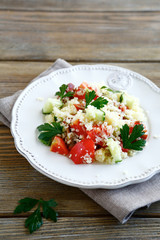 Salad with cooked couscous and fresh vegetables on a plate