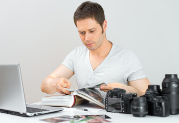 Male photographer watching photo album at his workplace.